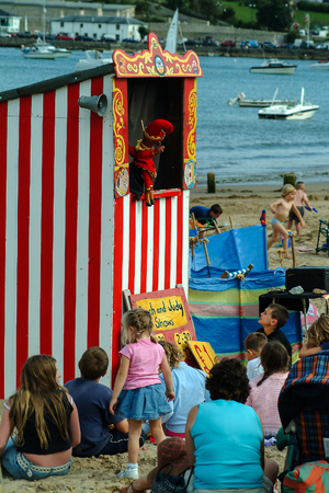 Plymouth, United Kingdom - August 28 2004:   Children watching a traditional Punch and Judy show on a beach near Plymouth