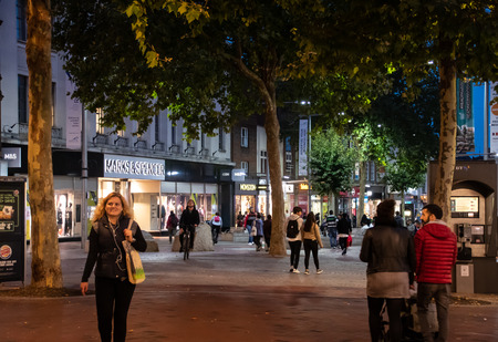Reading, United Kingdom - October 05 2018:   Shoppers after dark wander past Marks and Spencers, Monsoon and other Stores in Broad Street
