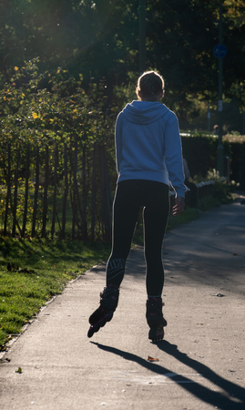 Basingstoke, United Kingdom - September 27 2018:   A young woman wearing Nike Leggings rollerblading into the Sunset in Eastrop Park