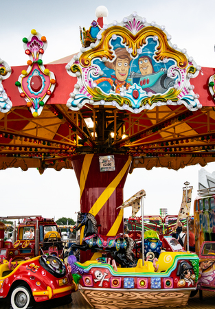 Netley Marsh, United Kingdom - July 21 2018:   A brightly coloured Merry Go Round with pirate ship, horse and car seats,  at Netley Marsh Steam Fair Banco de Imagens - 124731178