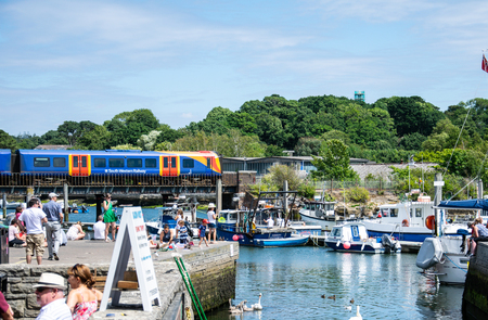 Lymington, United Kingdom - July 22 2018:   A South Western Train  crosses the tracks behind the harbour to Lymington pier station
