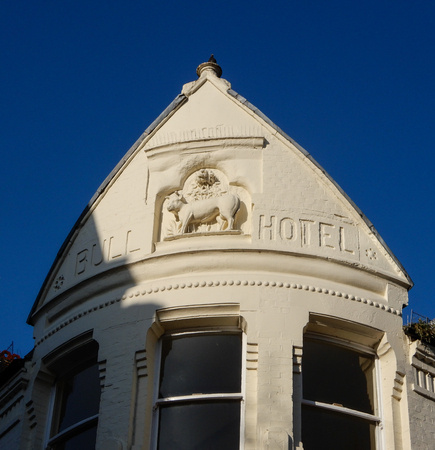 Reading, United Kingdom - April 20 2018:   The sign of the now defunct Bull Hotel, carved into the eaves of the roof.