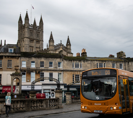 Bath, United Kingdom - October 13 2018:   A number D3 bus passes shops with the Cathedral behind on North Parade