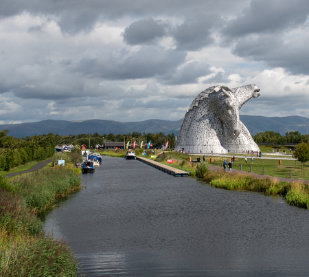 Falkirk, United Kingdom - August 09 2018:   Tourists around the Kelpies - a pair of large horse head statues made from Stainless steel by Sculptor Andy Scott and unveiled in 2013 along side the Forth and Clyde canal Publikacyjne