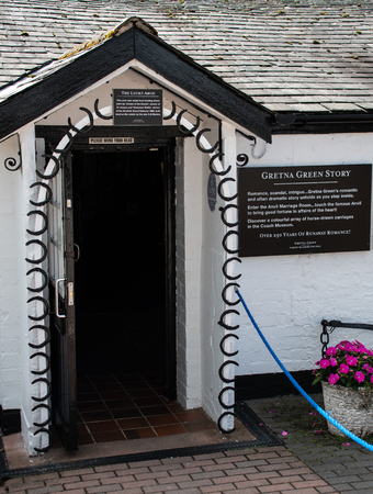 Gretna Green, United Kingdom - August 08 2018:   A doorway decorated with horseshoes for good luck, used by couples getting married at Gretna Greens Famous Blacksmith marriage centre