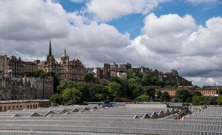 Edinburgh, United Kingdom - August 10 2018:   The roof of Waverley Train Station beneath the ancient buildings of Edinburgh seen from North Bridge