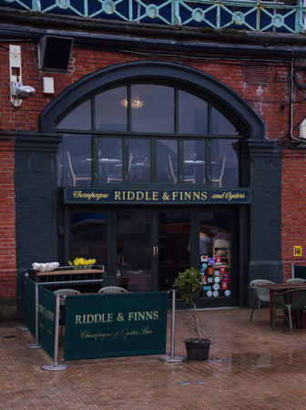 Brighton, United Kingdom - March 28 2018:   The frontage of Riddle and Finns, a seafood restaurant in the seafront arches under Kings Road
