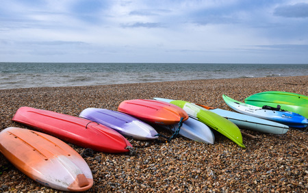 Brighton, United Kingdom - March 29 2018:   A Collection of Colourful Kayaks laying on Brighton beach Publikacyjne