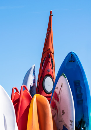 Barton on Sea, United Kingdom - July 22 2018:   A collection of colorful canoes surfboards and body boards stood upright Publikacyjne