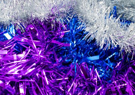 A pile of tinsel in silver, purple and blue