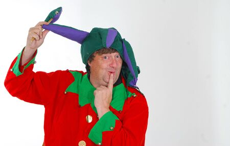 A portrait of a middle aged man dressed as a jester in a foolish pose and with a silly expression against a white background