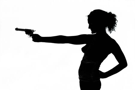 Reading, United Kingdom - August 09 2005:   Silhouette of a woman firing a revolver held in her outstretched arm, taken in a studio