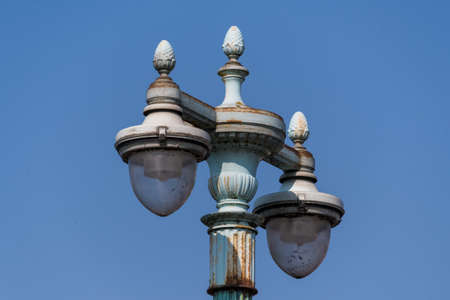The top of an old style lamp post on a sunny day