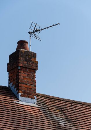 A analogue TV Aerial attached to a chimney on a roof top Stock Photo