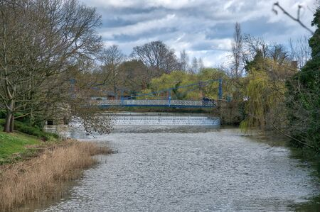 A foot bridge crosses the RIver Learn behind the Jephson Gardens Weir