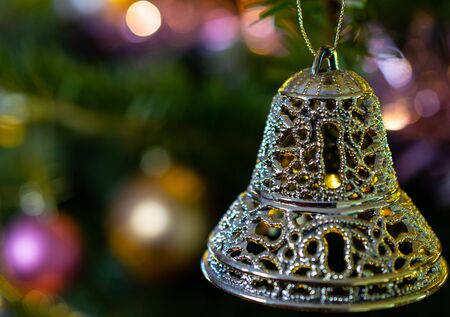 A Festive bell decoration hanging on a Christmas Tree