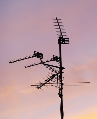 A pole mounted with several television aerials seen against a sunset sky Stock Photo