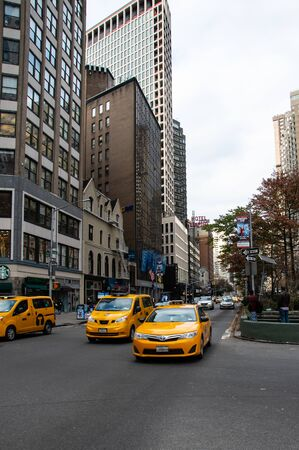 New York City, United States - November 17 2018:   Three New York Yellow Taxis pulling away from Traffic lights on Central Park West