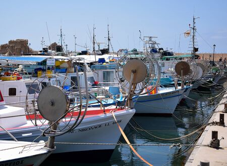 Paphos, Cyprus - May 26 2015:  A line of fishing boats with large prow mounted net reels tied up in Paphos harbour Редакционное
