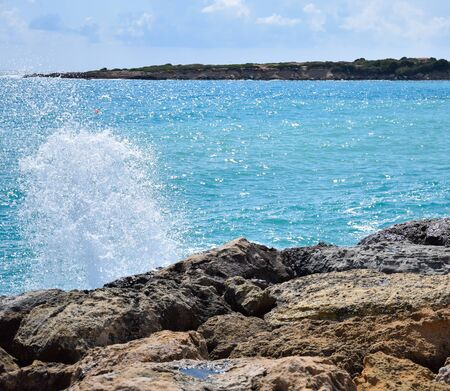 The blue waters of the Mediterranean sea breaking agianst the rocks on Laourou Beach