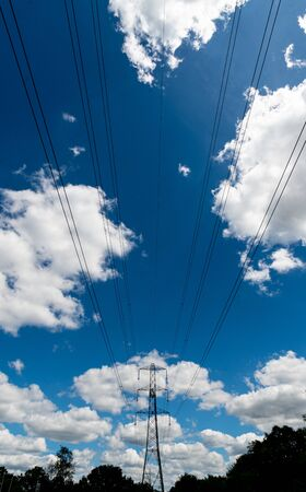 An electricity pylon with wires passing over head on sunny day.