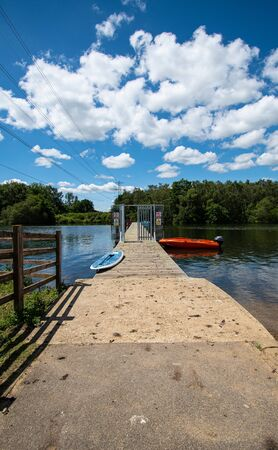 A dinghy and an sailboard moored on the jetty at Horseshoe Lake
