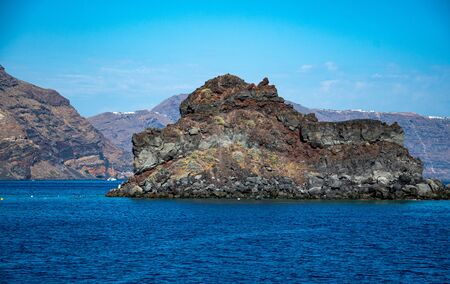 A rock rises out of the Aegean sea just off the coast of Santorini Archivio Fotografico