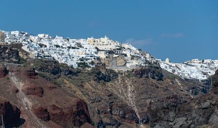 View from the Aegean sea of the clifftop town of Oia on the island of Santorini