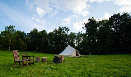 A Yurt, or round tent, with chairs and logs outside on a Glamping site in the Cotswolds