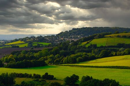 A cloudy sky looms over the fields hills and villages of the Costwolds 版權商用圖片