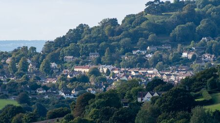 A view of the Cotswolds town of Alderley nestled in the trees and hills.