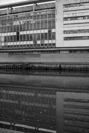 A 1970s architecture building reflected in canal water 版權商用圖片