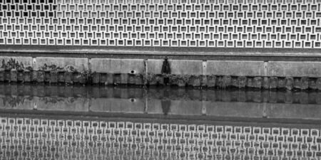 A 1970s decorative wall reflected in the water of a canal.