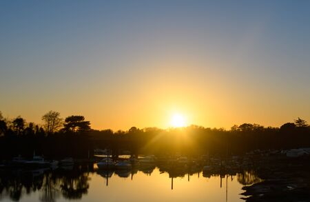 The sun setting over a Boatyard on the River Hamble seen from the M27