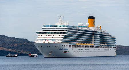 Fira, Greece - July 16 2019:   The Itailan based Cruise ship Costa Luminosa anchored in the Aegean Sea off the coast of Santorini near Fira Editorial