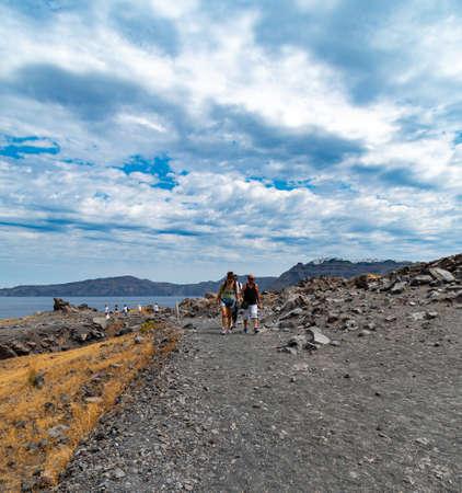 Nea Kameni Island, Greece - July 16 2019:   Tourists wend their way along the path leading to the peak of Santorini's volcanic centre on Nea Kameni Island Editorial