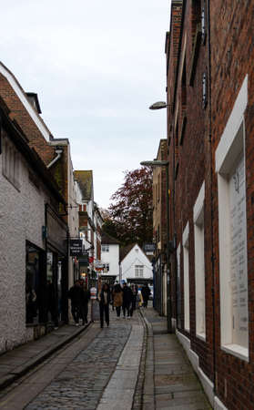 Guildford, United Kingdom - November 06 2019: Shoppers and stores along the tiny side street The Shambles