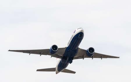 Heathrow, United Kingdom - August 03 2019:  British Airways Boeing 777-236 registration G-VIIC,  flight number BA125 departs Heathrow airport en route to Bahrain seen from Myrtle Avenue