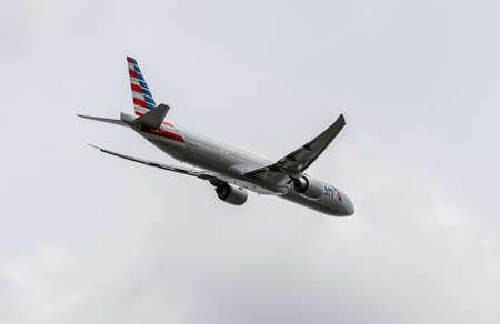 Heathrow, United Kingdom - August 03 2019:  American Airlines Boeing 777  registration N717AN flight number AA39 departs Heathrow airport en route to Miami seen from Myrtle Avenue
