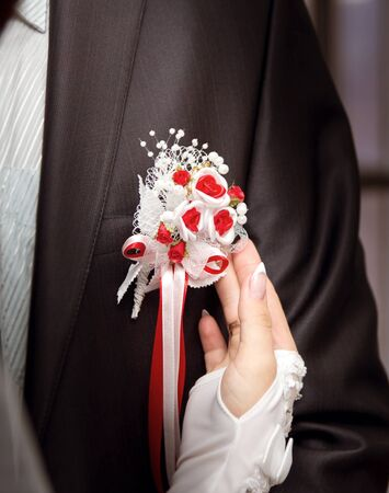 boutonniere: Bride putting on flower boutonniere on groom in black suit Stock Photo