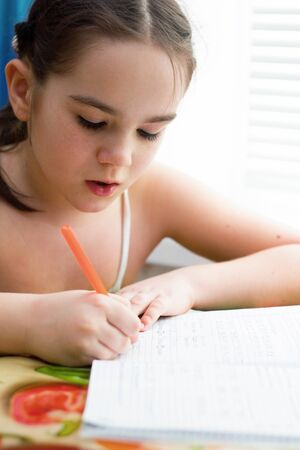 wrote: Girl wrote in a notebook Stock Photo