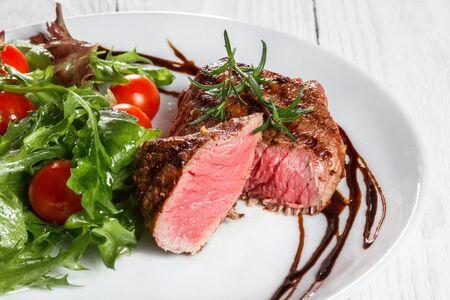 animal origin: steak and salad on a plate