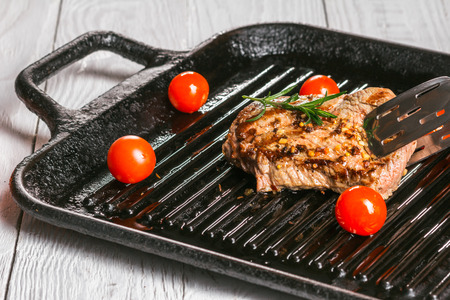 scatter: steak holding forceps and cherry tomatoes in a pan