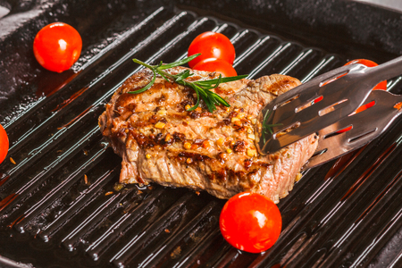 animal origin: steak holding forceps and cherry tomatoes in a pan