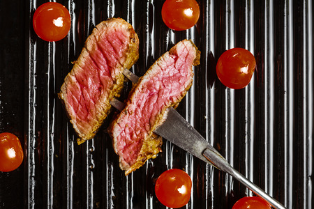 animal origin: Slices of beef steak on meat fork and cherry tomatoes Stock Photo
