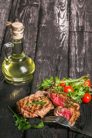 animal origin: steak and salad on a wooden table Stock Photo