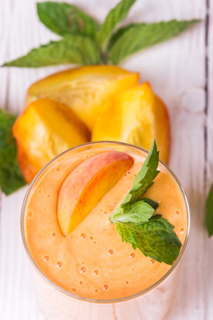 Smoothie in a glass and slices of fresh peaches Stock Photo