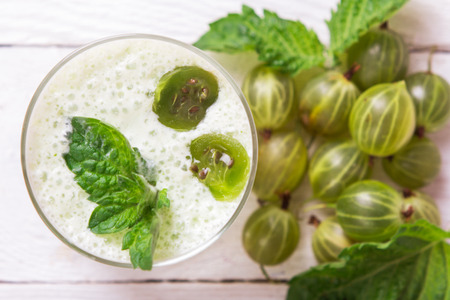 Smoothie in a glass and fresh gooseberries