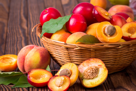 Whole and half peaches, plums and apricots in a basket