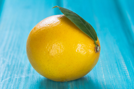 lemon wedge: ripe yellow lemon on a blue wooden table Stock Photo